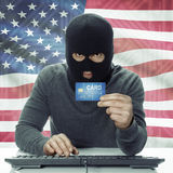 Dark-skinned hacker with flag on background holding credit card in hand - United States Royalty Free Stock Photos