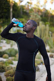 Dark-skinned healthy man with beautiful body drink water after workout outdoors. Attractive fit man in active clothes refreshing with water after run, dark Royalty Free Stock Images
