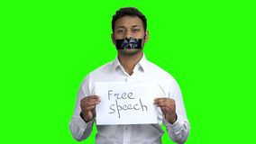 Dark-skinned man with black tape over mouth. Alpha Channel background. Free speech concept stock footage