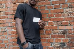 Dark-skinned man in T-shirt showing blank business card on bricked background. royalty free stock photo