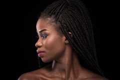 Dark skinned model with turning head to the left side on black backstage. Royalty Free Stock Image