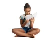Dark-skinned teen girl reading e-book Stock Photos