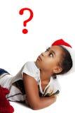 Dark-skinned teen girl surprised. The girl in the hat of Santa. Claus looking up Stock Image
