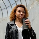 A beautiful young African American woman in a leather jacket holds a black glass against the background of an old cracked wall. A royalty free stock image