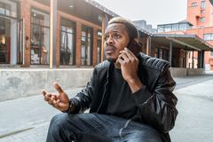 Dark-skinned unpleasantly surprised and annoyed man talking by mobile phone. stock photography