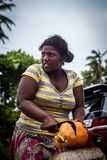 A dark-skinned woman cuts an orange coconut with a big knife. Working hard women. Strong and worthy woman doing hard job. Bentota, Sri Lanka - 6 March 2014. a royalty free stock photos