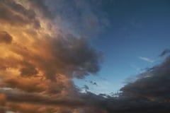 Dark sky with blak clouds brings storm rain at the sunset Stock Photos