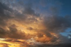 Dark sky with blak clouds brings storm rain at the sunset Royalty Free Stock Images