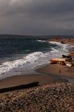Dark sky and churning surf Stock Photos