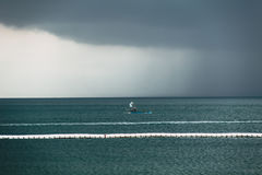 Dark sky cloud rain strom in the sea. In rainy season with alone fishing boat Royalty Free Stock Images