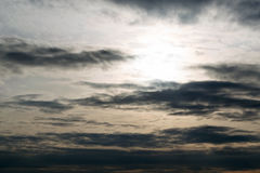 The dark sky, the evening sun, the clouds in a line along the horizon. Stock Images