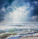 Dark sky on a stormy sea. Rays of light from the dark sky on a stormy sea Stock Photos