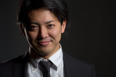 Dark and Smiling Asian Male Portrait Stock Images