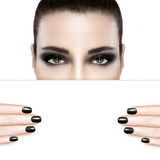 Dark smoky beauty and nail art concept. With a woman wearing creative dark eye makeup holding a blank white card template covering her mouth with matching dark Royalty Free Stock Image