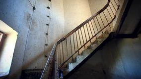 Dark spiral staircase with window into a stock video