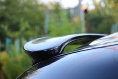 Dark spoiler car, mirroring sky, village style, green background stock image