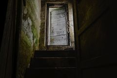 Dark stairs with old and white door leading down to dark basement stock photo