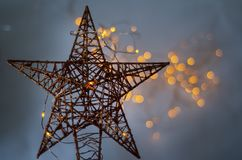 a gold star made of wire with yellow lights in the background stock image