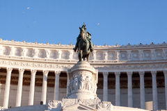 Dark statue and white building. A dark equestrian statue in fron of white official building in Roma stock image