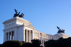 Dark statue and white building. A dark equestrian statue in fron of white official building in Roma royalty free stock images