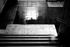 Rain puddles at the stairs. The dark steps of a station tunnel with puddles and damp walls Stock Images