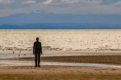 A Silhouette figure facing the horizon at Crosby Beach,England. A dark still silhouette figure facing the horizon at an empty Crosby beach,Merseyside,England royalty free stock photos