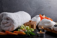 A set of bath towel, candles, pebbles and grapefruit for a spa treatment. On a dark stone background a set of white bath towel, aroma of candles, pebbles and Stock Images
