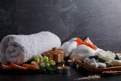 Set of towel, aroma of candles, flowers, different stones and grapefruit for a spa treatment. On a dark stone background a set of white bath towel, burning Royalty Free Stock Photography