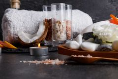 A set of towels, coconut, candles, different stones for a spa treatment. On a dark stone background a set of white bath towels, several pieces of fragrant Stock Image
