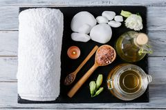 On a dark surface is a bath towel, oil and various stones for spa treatments. On a dark stone surface there is a white bath towel, aroma of oil and various Stock Photography