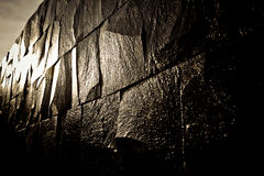 Dark stone wall shining with the light Stock Photos