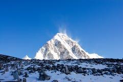 Dark stones, white Mount Pumori, blue sky Stock Photos