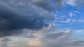 Dark storm-cloud cover blue sky with white clouds at sunny day. Time lapse stock video footage