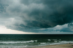A dark storm cloud hovers over the Atlantic Ocean. Stock Photo
