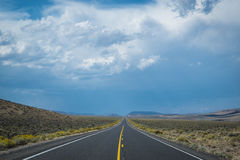 Dark storm clouds above desert highway Royalty Free Stock Photos