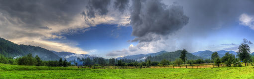 Dark storm clouds over mountains. And green rice fields with small wooden buildings royalty free stock photo
