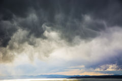 Dark storm clouds over the sea. Stock Photos