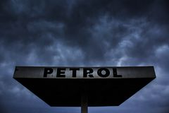 Ominous Sign of the Times. Dark storm clouds roil above the roof of a gas station. Human dependence on fossil fuels does not bode well for life on earth royalty free stock photography