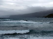 Dark stormy atlantic ocean waves breaking on rock and the beach Royalty Free Stock Image