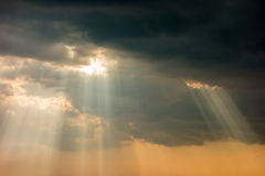 Dark stormy clouds. Stormy sky with a dramatic sunrays between the clouds on spring evening in Greece Stock Photos