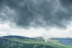 Dark clouds under hill. Dramatic background. Dark stormy clouds under hill. Dramatic background stock photos