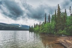 Dark stormy clouds under lake. Dramatic landscape. Dark stormy clouds under lake and forest. Dramatic landscape stock image