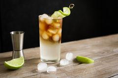 Dark and Stormy Cocktail. Dark and Stormy Rum Cocktail with Ginger Beer and Lime garnish. Glass of Dark and Stormy Cocktail drink on wooden table, copy space stock image