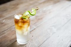 Dark and Stormy Cocktail. Dark and Stormy Rum Cocktail with Ginger Beer and Lime garnish. Glass of Dark and Stormy Cocktail drink on wooden table, copy space stock photo