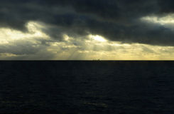 Dark Stormy Sky with Golden Sunshine Rays, Cargo Ship Royalty Free Stock Images