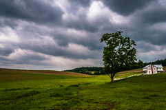 Dark stormy sky over trees and a house in York County Stock Photos