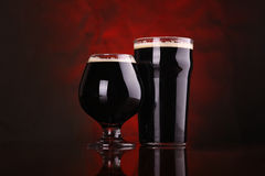 Dark stout beer. Nonic pint and snifter of dark stout beer on a wooden table over a redish background Royalty Free Stock Photography