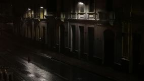 Dark street with few lamp posts and people running through heavy rain during a dark night stock video footage