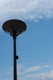 Dark street light isolated with cloudy blue sky stock photos