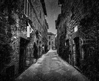Dark street in an old Italian town in Tuscany, Italy. Raining, black and white Stock Photo